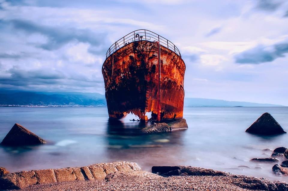 An oxidised shipwreck in calm waters.